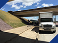 Fabick's mobile unit on a state highway project applying a epoxy coating to crushed aggregate used for slope paving.