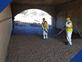 A Fabick applicator coating crushed aggregate used as slope paving with an epoxy coating.