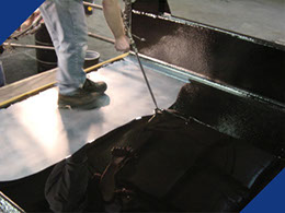 A Fabick aromatic polyurethane being Poured-On® a truck bed as an industrial protective coating.