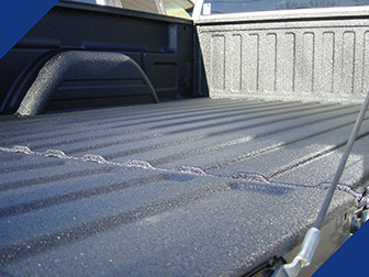 Fabick sprayed-on bedliner applied in black to a pickup truck bed.